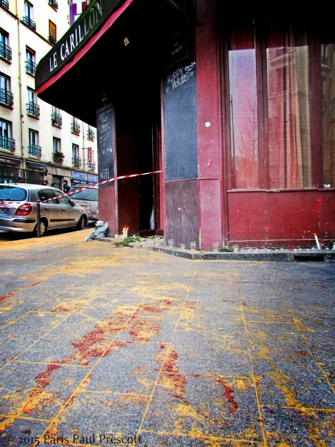 Blood stains drying in sawdust in front of the Carillon Hotel